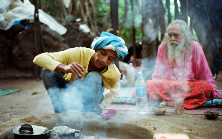 Indian baba and his friend sitting under the big banyan tree  making fire